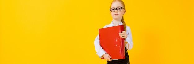 Meisje met rood haar op een gele muur met map