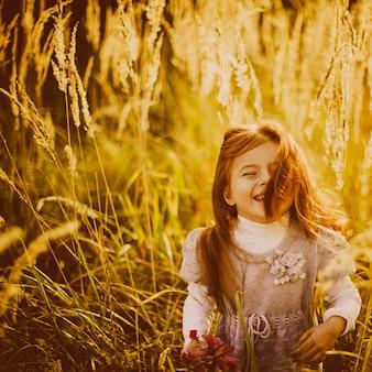 Meisje met rood haar staat op het gebied van de herfst