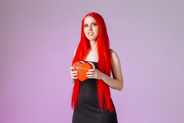 Meisje met rood lang haar met geschenkdoos op roze achtergrond