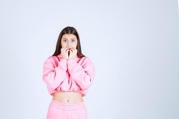 Meisje met roze pyjama ziet er bang en doodsbang uit
