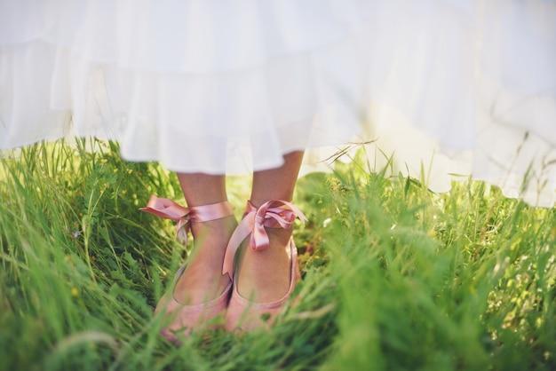 Meisje met roze schoenen op het gras