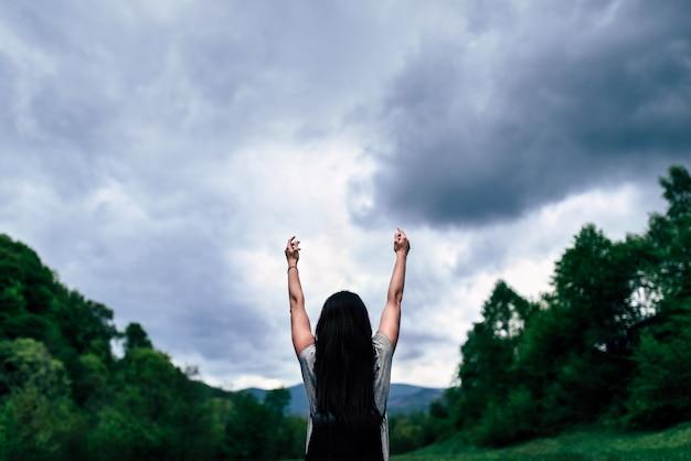 Meisje met rugzak in de bergen met bewolkte hemel