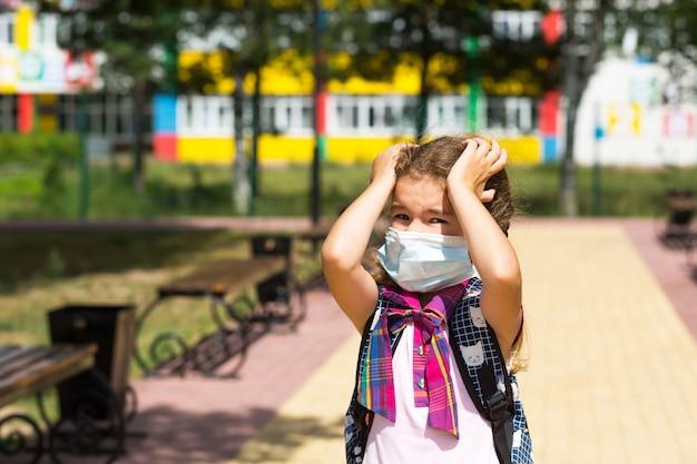 Meisje met rugzak in de buurt van de school nadat de lessen een medisch masker hebben afgezet, ongelukkig, moe en hoofdpijn