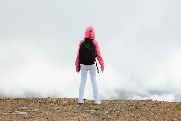 Meisje met rugzak op zoek op prachtige bergen in de wolken