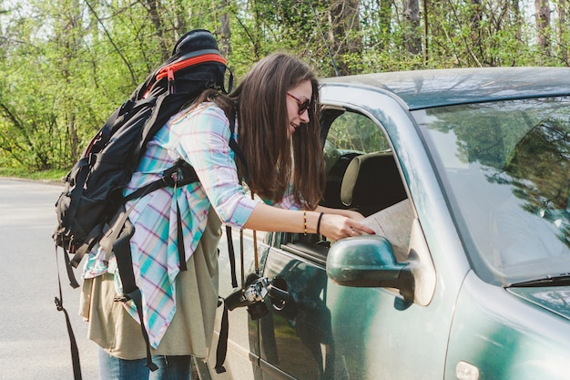 Meisje met rugzak praten met een chauffeur