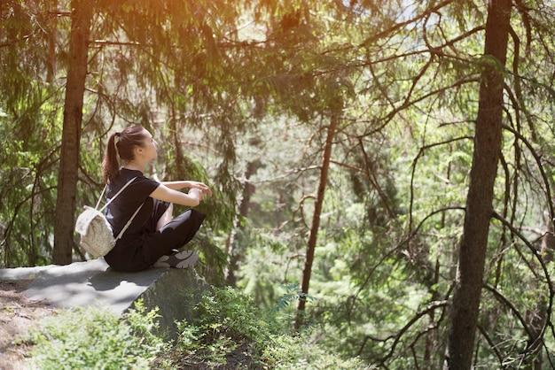 Meisje met rugzakzitting op een rots in het bos. zonnige zomerdag