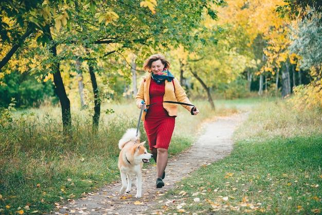 Meisje met schattige jonge foxy hond loopt langs traject onder herfstbladeren in herfst park