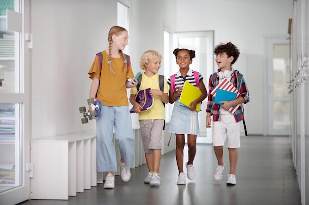 Meisje met skateboard wandelen met jonge leerlingen langs de gang van de school