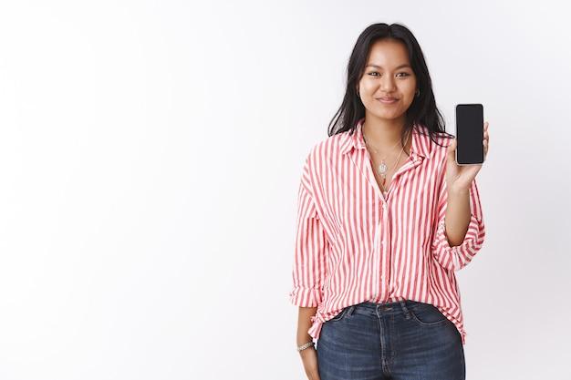 Meisje met smartphone stelt ze voor om te kopen. opgetogen gelukkige aantrekkelijke jonge polynesische vrouw in gestreepte roze blouse met mobiele telefoon presenteren app op gadget scherm op witte achtergrond