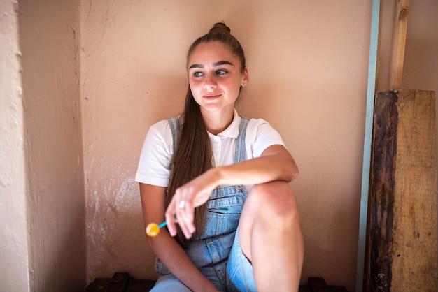 Meisje met snoep op een stokje in een verwoest huis. foto van hoge kwaliteit