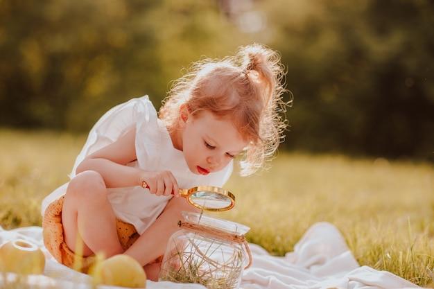 Meisje met staart spelen met vergrootglas in het park. zomer. ruimte kopiëren.