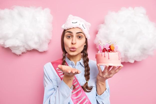 Meisje met staartjes stuurt luchtkus houdt lippen gevouwen houdt palm naar voren lippen draagt slaapmasker shirt en lint houdt smakelijke feestelijke cake met brandende kaarsen geïsoleerd op roze
