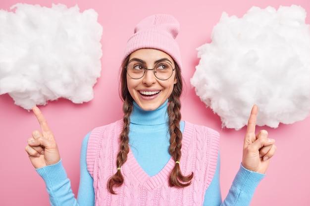 Meisje met staartjes wijst hierboven op witte wolken laat zien dat iets een hoed draagt, een coltrui, een ronde bril en een vest geïsoleerd op roze