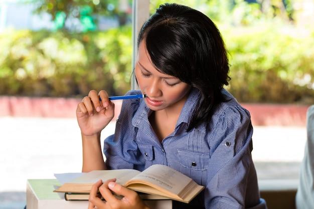 Meisje met stapel boeken leren