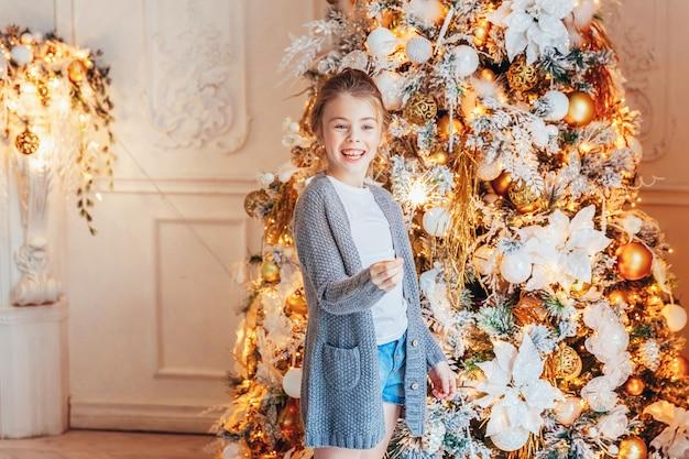 Meisje met sterretje in de buurt van de kerstboom thuis
