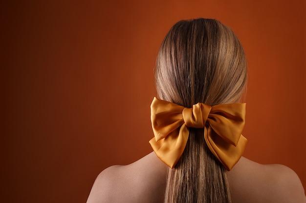 Meisje met strik in haar haar, achteraanzicht. naakte vrouw terug op oranje achtergrond