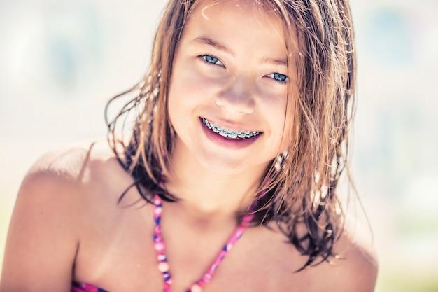 Meisje met tandensteunen portret van een schattig klein meisje op een zonnige dag in bikini