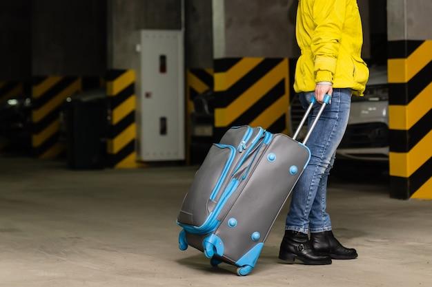Meisje met tas op de parkeerplaats op de luchthaven