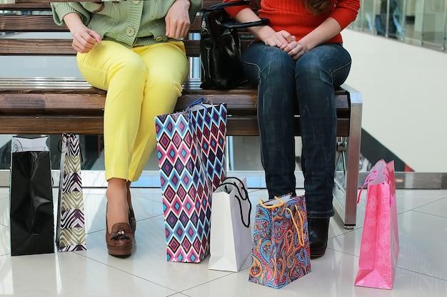 Meisje met tassen wandelen met zijn vriendin in het winkelcentrum en winkelen