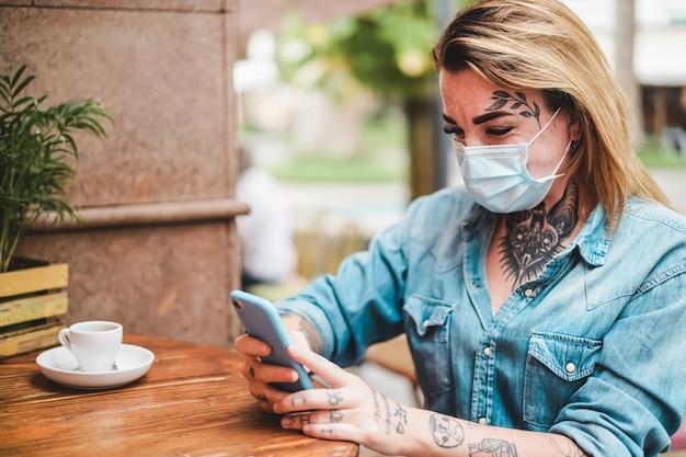 Meisje met tatoeage met behulp van mobiele telefoon terwijl het dragen van beschermend gezichtsmasker zittend in cafetaria