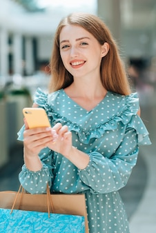Meisje met telefoon poseren in winkelcentrum