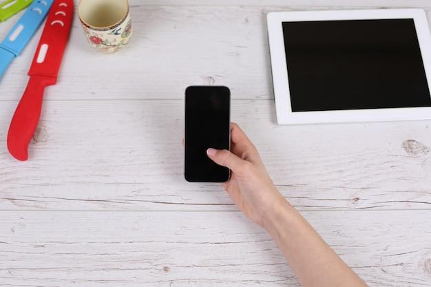 Meisje met telefoon tablet liggend op de houten tafel