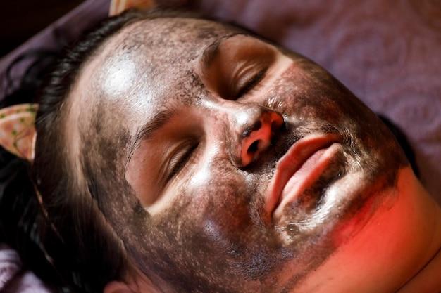 Meisje met therapeutische modder gezichtsmasker. cosmetische ingreep voor het gezicht. huidverjonging. hoge kwaliteit foto