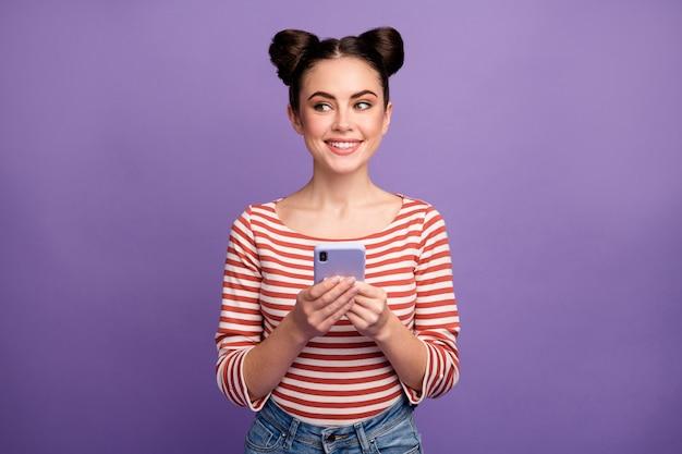Meisje met trendy kapsel met behulp van telefoon geïsoleerd op paars