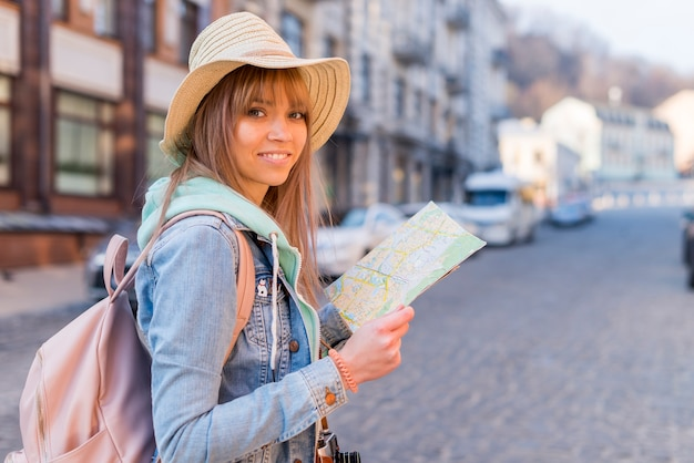 Meisje met trendy look locatie kaart in de hand kijken naar de camera