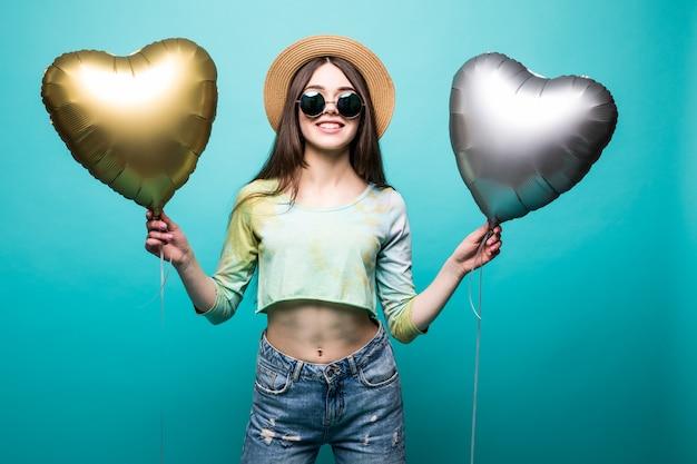 Meisje met twee ballonnen. de mooie jonge baloon van de vrouwenholding en het glimlachen terwijl geïsoleerd