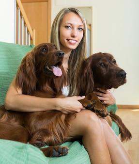 Meisje met twee ierse setters thuis