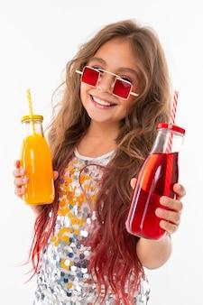 Meisje met twee kleurrijke coctails glimlacht bij camera