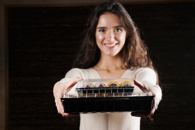 Meisje met twee sushidozen op zwarte achtergrond