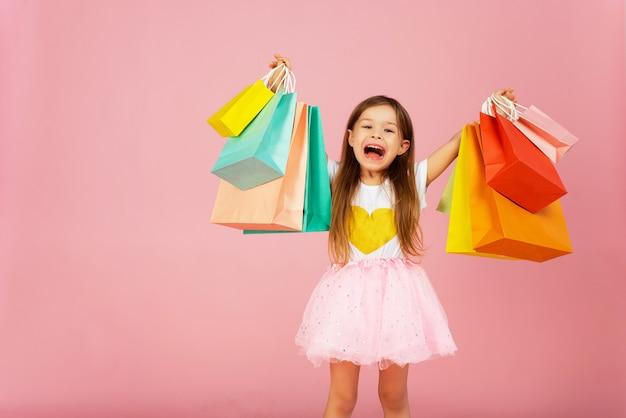Meisje met veel boodschappentassen op pastel roze achtergrondkleur. mooie zoete momenten van kleine prinses, mooi vriendelijk kind dat plezier heeft voor de camera