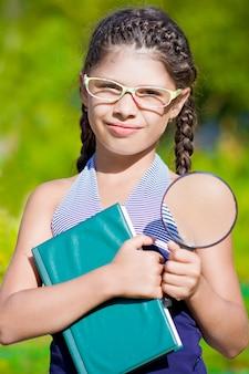 Meisje met vergrootglas en boek