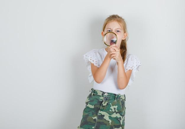 Meisje met vergrootglas en schreeuwen in wit t-shirt