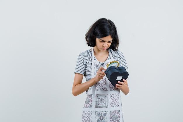 Meisje met vergrootglas over geschenkdoos in t-shirt, schort