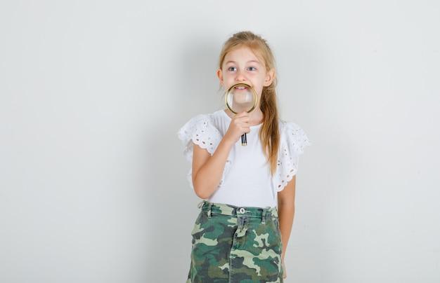 Meisje met vergrootglas over kin in wit t-shirt
