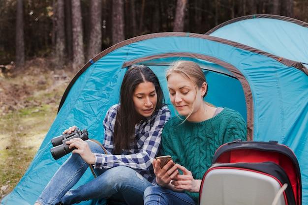 Meisje met verrekijkers en kijken naar haar vriend mobiele telefoon