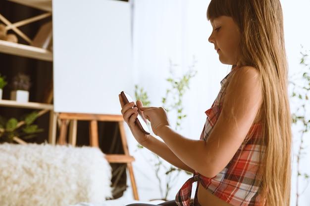 Meisje met verschillende gadgets thuis. klein model zit in haar bed met smartphone en maakt selfie of gebruikt videochat met haar vrienden. concept van interactie van kinderen en moderne technologieën.