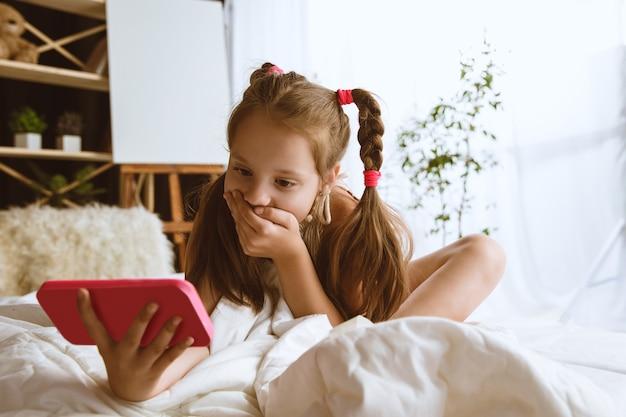 Meisje met verschillende gadgets thuis. klein model zit in haar kamer met smartphone en maakt selfie of gebruikt videochat met haar vrienden. concept van interactie van kinderen en moderne technologieën.