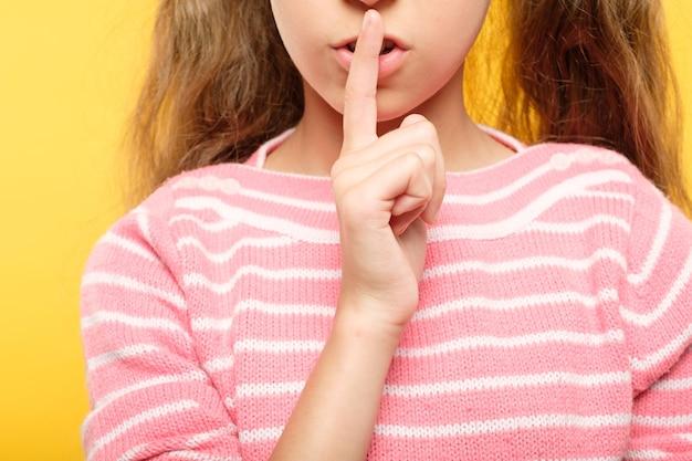 Meisje met vinger op lippen. ondeugend kindgeheim en samenzwering
