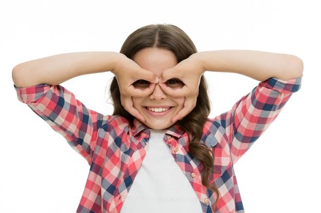 Meisje met vingers in de buurt van ogen zoals een bril maskeert superheld of uil. speel spel met masker superheld. kind vrolijke stemming gelukkig grimas met masker. doe alsof je een fantastische held bent. kid verbergen gezicht vinger masker.