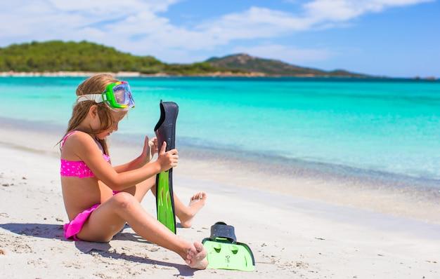 Meisje met vinnen en beschermende brillen voor het ssnorkling op het strand