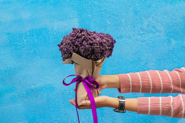 Meisje met violet boeket op blauwe muur
