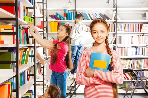 Meisje met vlecht staat in bibliotheek met notitieboekje en glimlacht