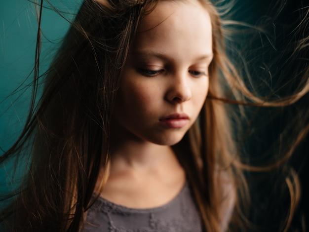 Meisje met wapperende haren poseren close-up groene achtergrond