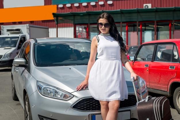 Meisje met wegkoffer dichtbij de auto