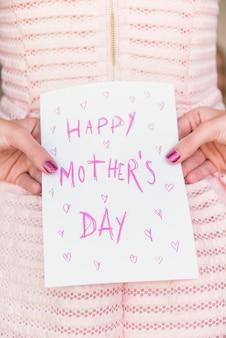 Meisje met wenskaart met happy mothers day inscriptie