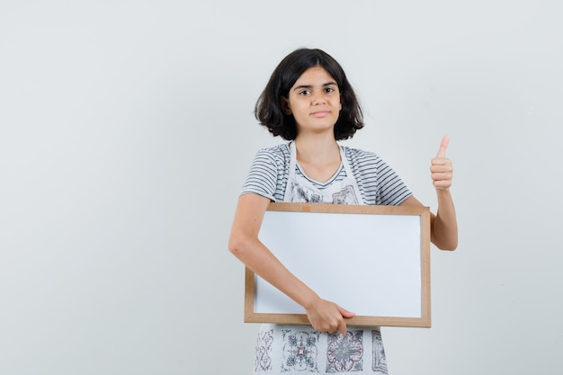 Meisje met wit frame, duim opdagen in t-shirt, schort